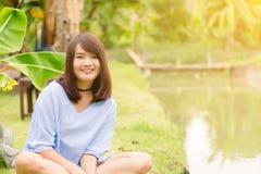 微笑与完善的微笑和白色牙在公园和看照相机的妇女 库存照片