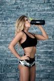 微笑与愉快的新能量的健身妇女,当冒汗和从瓶时的饮用水 免版税库存照片