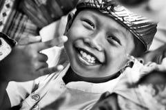 微笑与手势`我爱你`的一点甜巴厘语男孩 库存照片