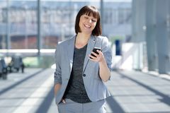 微笑与手机的专业女商人 免版税库存照片