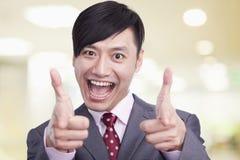 微笑与有他的手指的嘴开放制造的手枪的年轻商人画象对照相机 库存照片