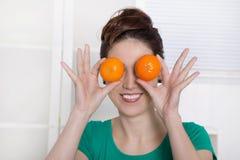 微笑与橙色眼睛的少妇。 库存图片