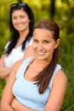 微笑与母亲的青少年的女孩在背景中 免版税库存图片