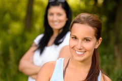 微笑与母亲的青少年的女孩在背景中 免版税库存照片