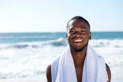 微笑与毛巾的愉快的人对海滩 免版税图库摄影
