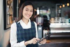 微笑与片剂在她的手上,女性emplo的亚洲妇女barista 免版税库存照片