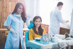 微笑与牙齿诊所的女性患者的牙医 免版税库存图片
