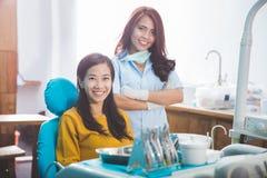 微笑与牙齿诊所的女性患者的牙医 免版税库存照片