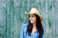 微笑与牛仔帽的可爱的年轻深色的妇女 库存图片