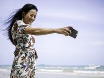微笑与生气勃勃面孔的迷人的亚裔妇女,当在白色海滩时的selfie 库存照片