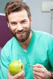 微笑与白色牙的年轻英俊的男性医生拿着苹果 库存照片