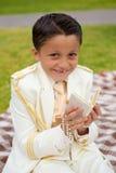 微笑与祈祷书和念珠的年轻人第一个圣餐男孩 库存照片