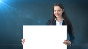 微笑与空白的白板的女商人画象在被隔绝的蓝色 与长的头发的女性模型 免版税图库摄影
