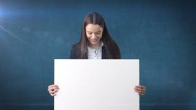微笑与空白的白板的女商人画象在被隔绝的蓝色 与长的头发的女性模型 库存照片