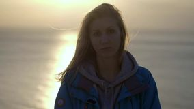 微笑与红色头发的年轻女人接近的画象吹在看在海洋女孩佩带的黄色的风日落 股票视频