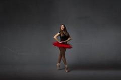微笑与红色芭蕾舞短裙的芭蕾舞女演员 免版税库存照片