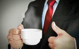 微笑与红色领带的商人喝一杯咖啡 库存照片