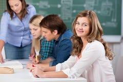 微笑与老师的十几岁的女孩协助同学对书桌 库存图片