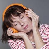微笑与耳机的平静的成熟妇女放松的 免版税库存照片