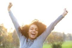 微笑与胳膊的快乐的年轻黑人妇女被举 免版税库存照片