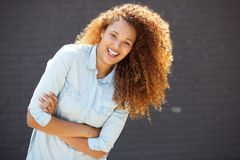 微笑与胳膊的愉快的年轻女人横渡由灰色墙壁 免版税库存照片