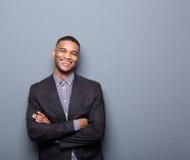 微笑与胳膊的愉快的年轻商人横渡 免版税库存图片