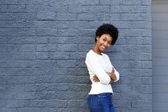 微笑与胳膊的确信的少妇横渡 免版税图库摄影