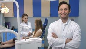 微笑与胳膊的英俊的男性牙医横渡 股票视频