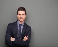 微笑与胳膊的英俊的年轻商人横渡 免版税图库摄影