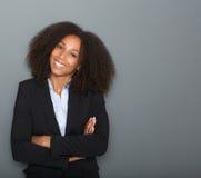 微笑与胳膊的年轻女商人横渡 免版税库存图片