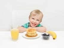 微笑与薄煎饼,莓果,禁令他的早餐的一个年轻男孩  免版税库存图片