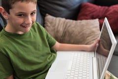 微笑与计算机的男孩 图库摄影