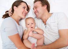 微笑与逗人喜爱的婴孩的一个愉快的妇女和人的画象 库存图片