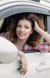 微笑与钥匙的美丽的司机妇女 免版税库存图片