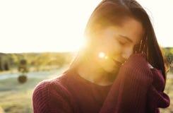 微笑与闭合的眼睛和res嘴唇,在自然背景的佩带的毛线衣的可爱的美丽的深色的年轻白种人妇女 免版税库存图片