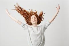 微笑与闭合的眼睛的年轻快乐的美丽的红头发人女孩画象震动在白色背景的头发 库存图片