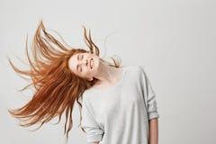 微笑与闭合的眼睛的年轻快乐的美丽的红头发人女孩画象震动头和头发在白色背景 免版税库存照片