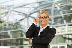 微笑与玻璃的愉快的女实业家在城市 免版税库存照片