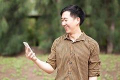 微笑与他的电话的年轻亚裔人在他的手上 库存照片