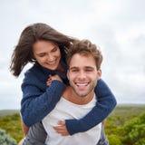 微笑与他的他的女朋友的年轻人 图库摄影