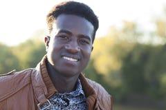 微笑与defocused树的英俊的年轻黑人在bac中 库存图片
