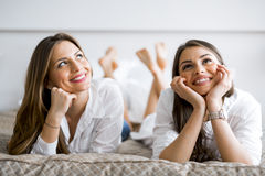 微笑两个美丽的女孩谈话和,当躺在床上时 库存图片