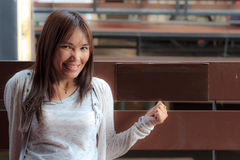 微笑亚裔妇女坐椅子。 免版税库存图片