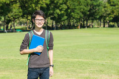 微笑亚裔的学生拿着书和,当站立在公园a时 免版税库存照片