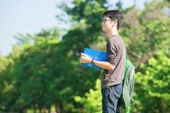 微笑亚裔的学生拿着书和,当站立在公园a时 免版税库存图片