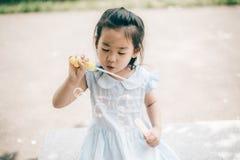 微笑亚洲女婴戏剧泡影气球 免版税库存照片