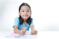 微笑亚洲小女孩图画画象与颜色铅笔的 库存照片