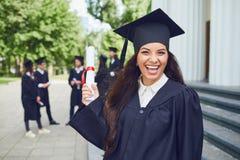 微笑以一个小组的毕业生女孩毕业生为背景 免版税库存图片