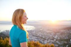 微笑作为太阳的少妇起来在城市 免版税库存照片