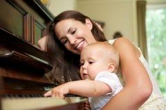 微笑作为婴孩的母亲弹钢琴 免版税图库摄影